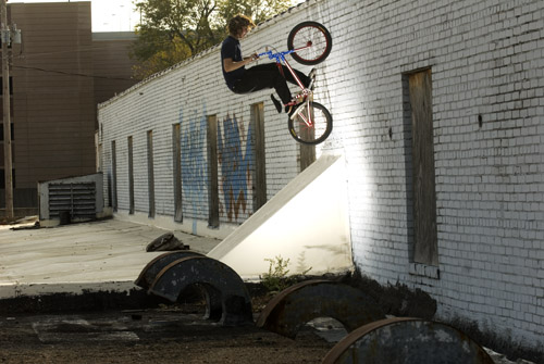 Justin Mann fakie on the roof of an abandoned warehouse